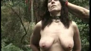 Gagged girl is in a tree while a stranger is touching her hairy pussy and soft lips